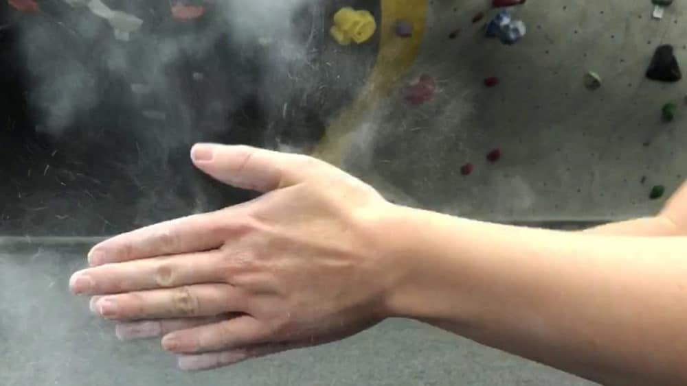 hands clapping chalk together